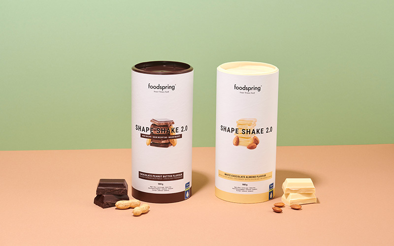 Two canisters of Shape Shake 2.0 meal replacement shakes in two flavors: chocolate-peanut butter and white chocolate-almond.