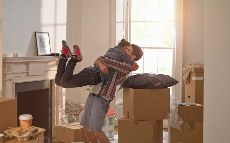 A man and woman hug in an unfurnished room full of boxes. The man is lifting the woman into the air and her feet are fully off the ground behind her.