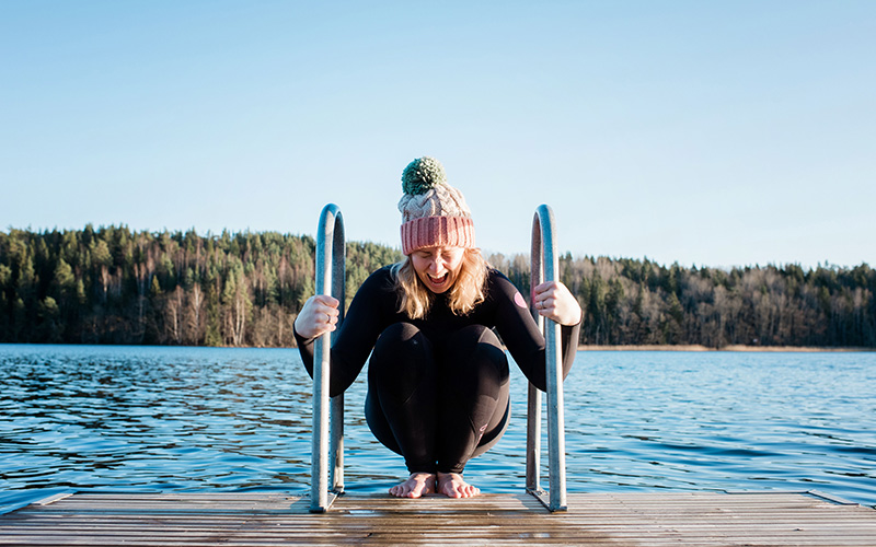 A white woman in a tassel hat and wetsuit prepares to jump into a lake backwards to initiate cold thermogenesis