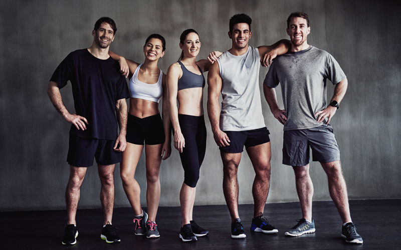 A photo of five smiling, athletic people: two women and three men, all in shades of black, white, and gray, showing how different bodies have different muscle fiber types