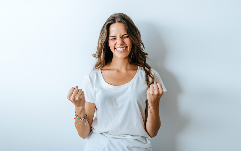 A white woman clenching her fists with both hands, making a face of hopeful wishing and using the WOOP method.