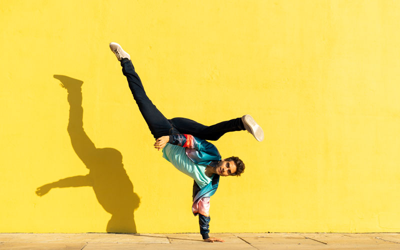 A white man does balance exercises on one hand in front of a yellow wall.
