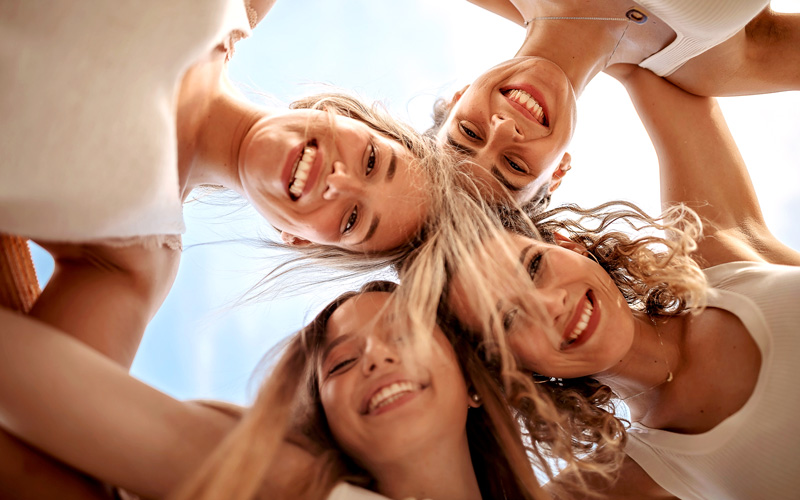 4 women look down towards the camera from above, their heads in a circle