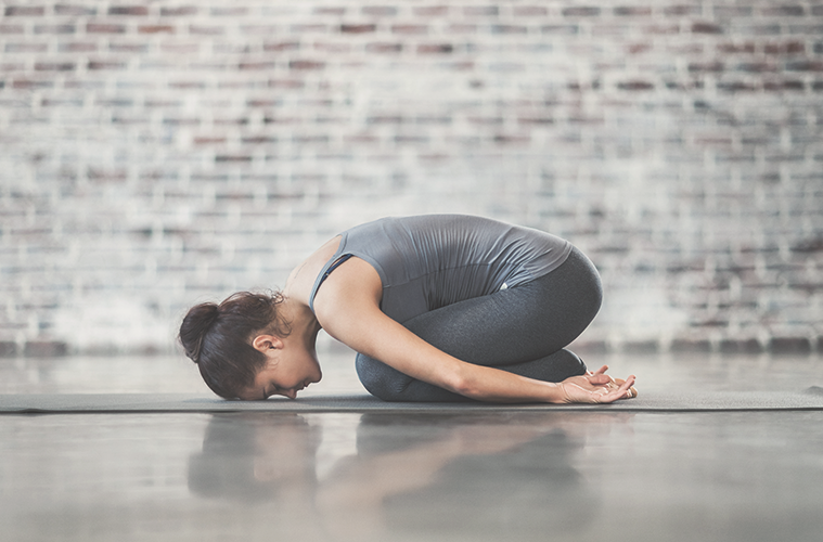 A white woman performs gentle yoga for muscle recovery. She wears gray clothes and is curled up, resting on her shins and forehead, in front of a gray brick background.