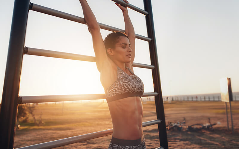 An athletic white woman is exercising in the heat doing pullups on an outdoor ladder with the sun at the horizon behind her