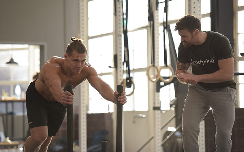 An athletic shirtless white man pushes a weight sled in order to achieve an afterburn effect after his workout