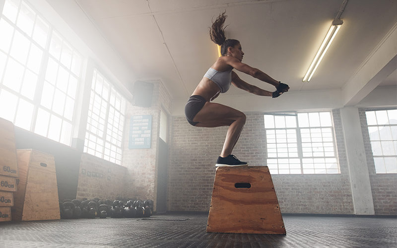 A white woman with long brown ponytail swinging above her head practices box jumps in hopes of achieving the afterburn effect