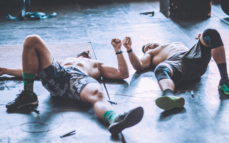 Two shirtless white men lie on the floor looking exhausted after a high-intensity workout