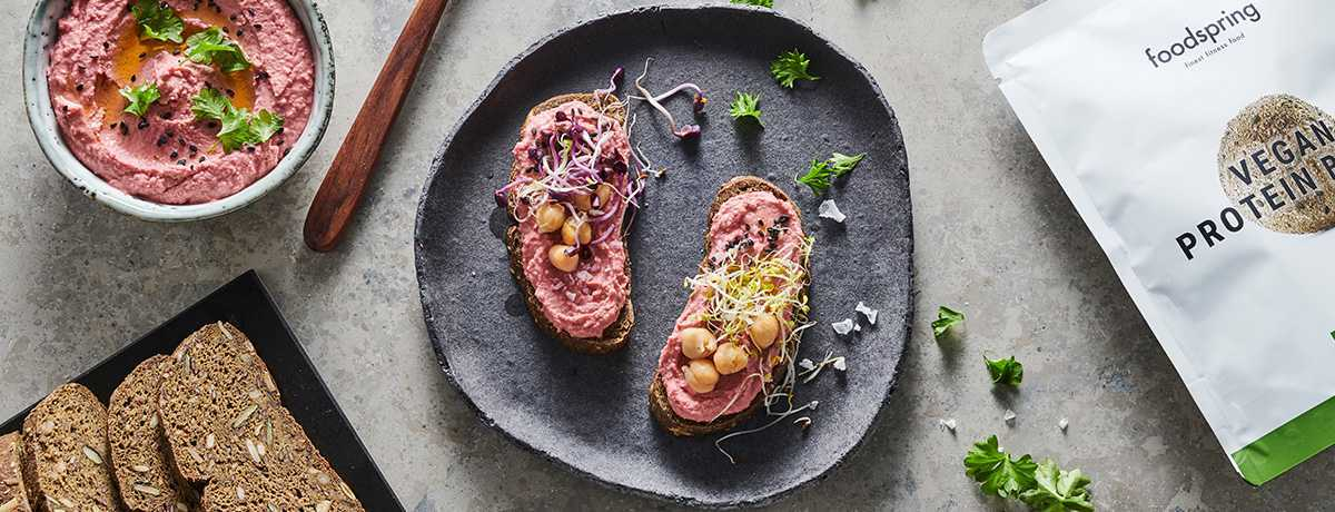 A gray plate seen from above holds 2 slices of Vegan Protein Bread topped with a dollop of beetroot hummus, and garnished with fresh sprouts and chickpeas.