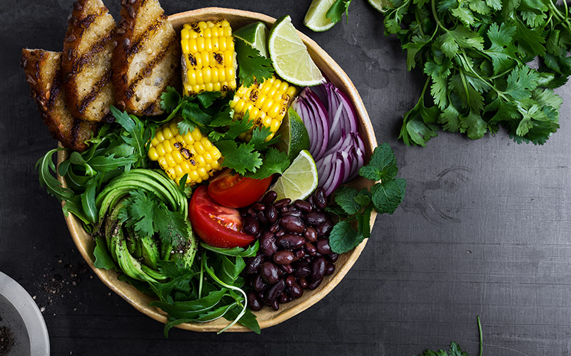 A bowl of deeply colored vegetables, tomatoes, corn, chicken strips with black grill marks, kidney beans, red onions, and green salad leaves sits on a gray background