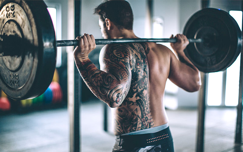 the tattooed back of a shirtless white man holding a weighted barbell on his shoulders, exercising for weight gain