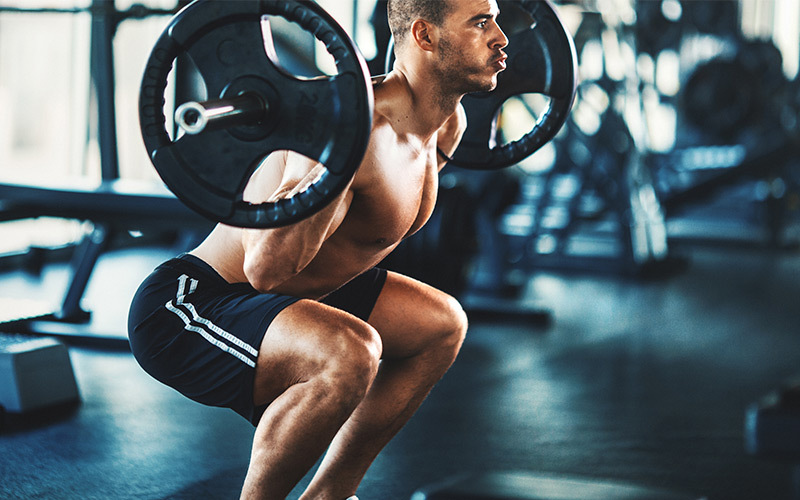 A shirtless, athletic man of color exhales as he squats with a weighted barbell on his shoulders