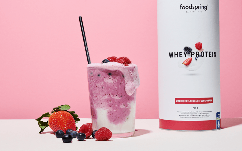 A wild berry whey protein shake sits next to the canister of Whey Protein mix