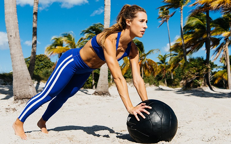 A white woman does push-ups on a large black ball on the beach, clearly a form of summer exercise