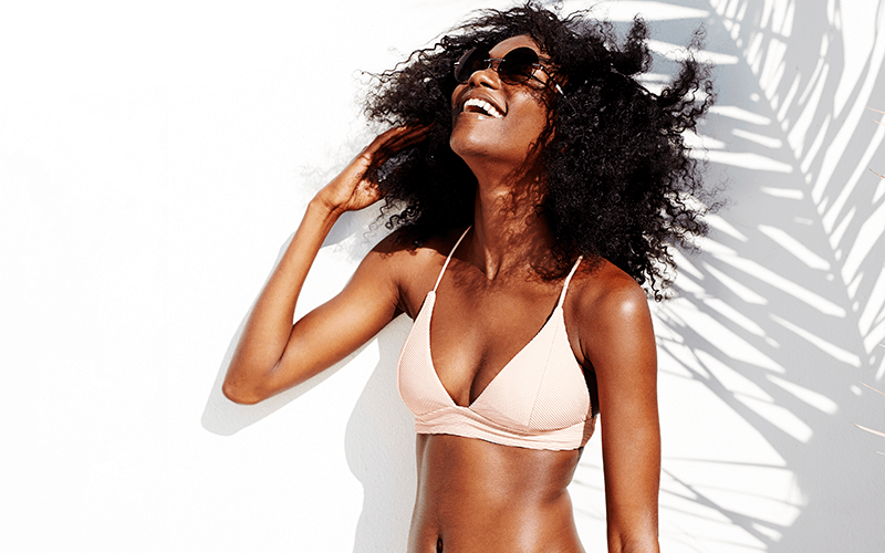 A woman of color in a bikini top shows an optimistic smile, brushing her curly natural hair away from her face as she looks upwards.