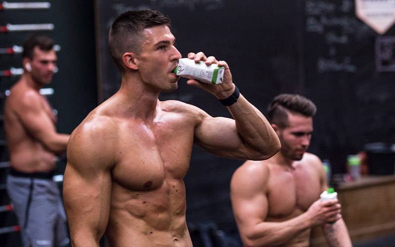 two shirtless, muscular, white-presenting men drink foodspring-branded beverages as part of their muscle hypertrophy workout
