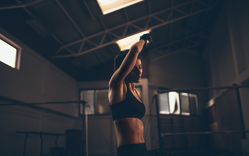 A woman in a dark room wipes sweat from her forehead with her arm after performing burpees