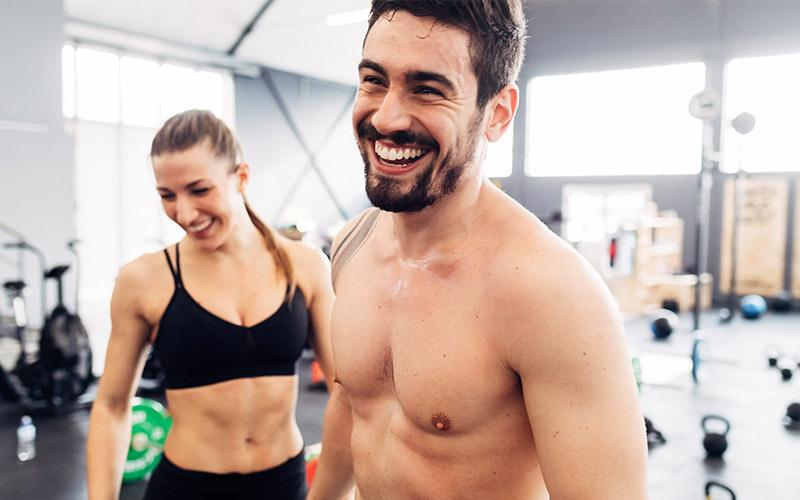 A smiling white man and woman prepare to do a couple workout in an indoor gym setting