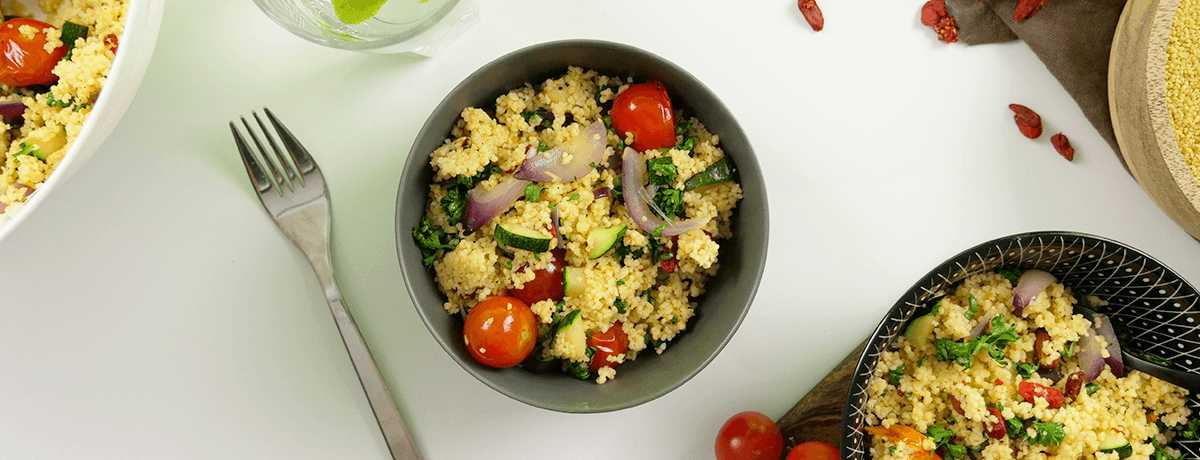 A bowl of couscous salad mixed with bright cherry tomatoes, red onions, zucchini, and vibrant green parsley is just one of many meal prep ideas
