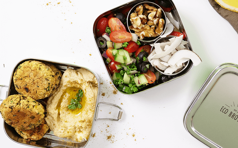 A stainless steel lunch box packed with hummus, falafel, and a tomato-cucumber salad is one of many fabulous meal prep ideas