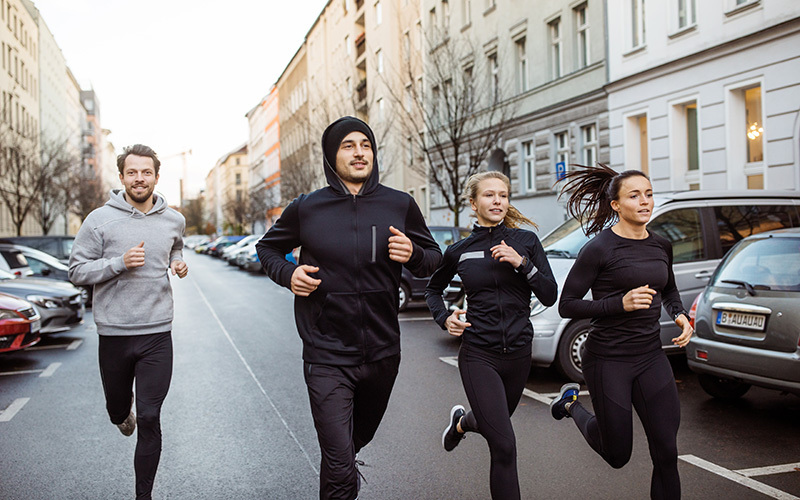 How to start jogging? Find friends to go with. In this photo a group of athletes in black and gray sports gear jogs together down a city street.