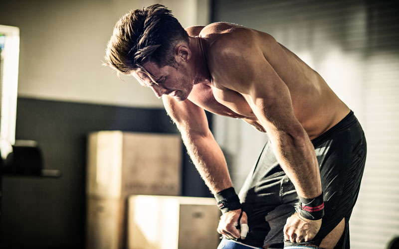 a shirtless white man practices breathing while lifting, as he leans his arms on his knees between sets