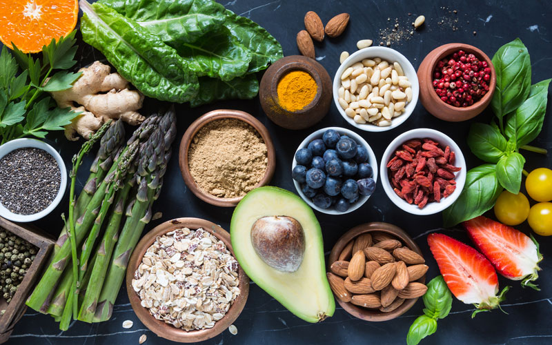 a group of appetite suppressant foods seen from above: avocadoes, blueberries, oats, asparagus, watermelon, and more
