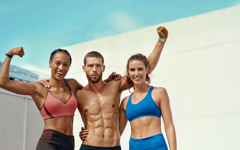 Three athletic people - two women and a man - showing their muscles. The women are in sports bras and the man is shirtless.