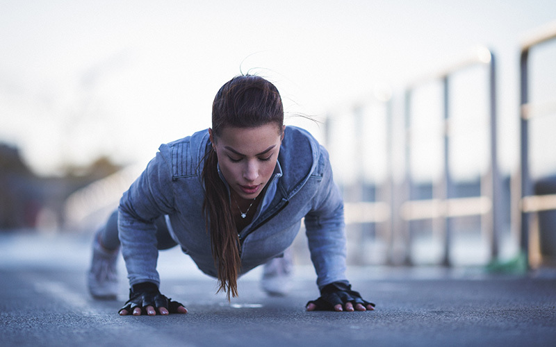 A white woman does push-ups outdoors