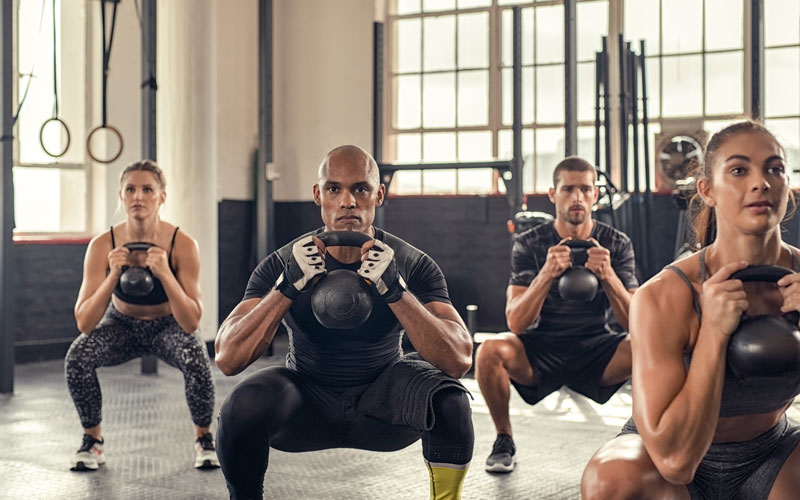 A group of athletes indoors working on progressive overload exercises with kettlebells