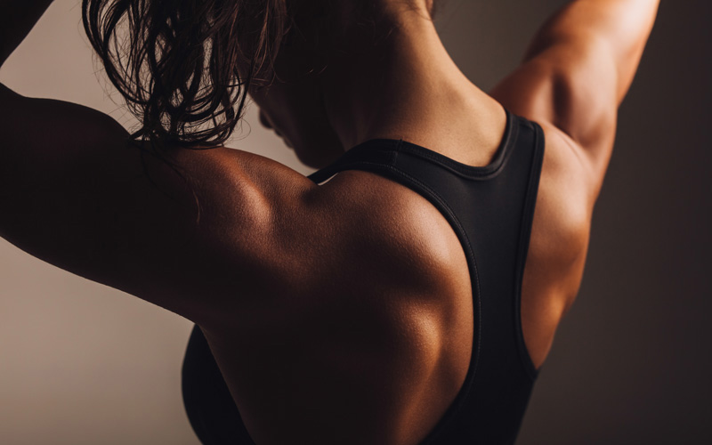 A view of a person in a black racerback sports bra from the back, showing muscle definition in their back and arms