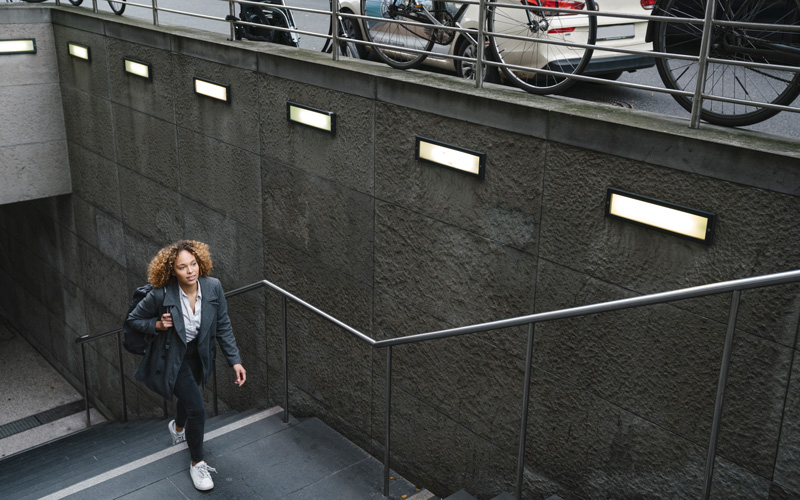 How to increase NEAT: try taking the stairs, as this woman of color is doing. She is climbing from an underground station to street level outdoors.