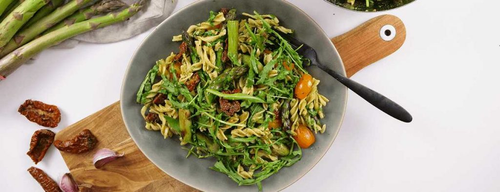 A green and fresh-looking bowl of pasta salad with asparagus, garnished with yellow cocktail tomatoes, dark red sun-dried tomatoes, and fresh green arugula leaves