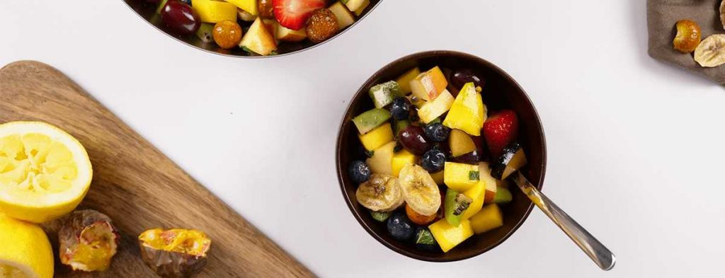 A black bowl holds bright, refreshing fruit salad with a spoon stuck into ot