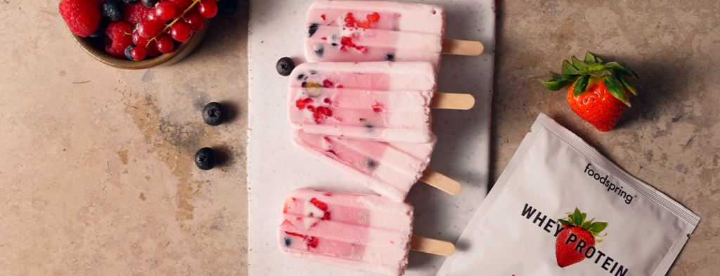 A stack of popsicles. Each berry yogurt popsicle has a smattering of berries at the top.