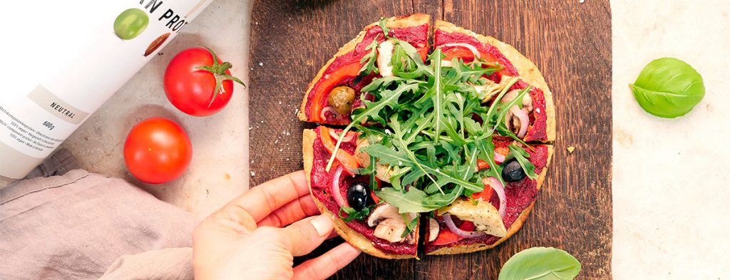 A high-protein vegan pizza dough topped with tomato sauce and green arugula sits on a wooden cutting board. A light-skinned hand reaches for a slice.