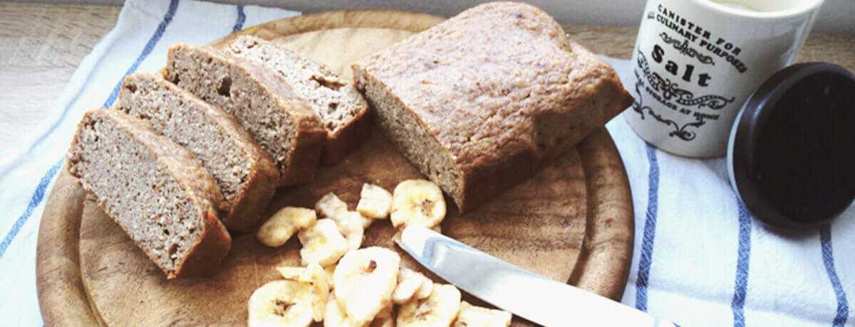 a photo of a sliced loaf of banana protein bread with a few banana slices on the side for garnish