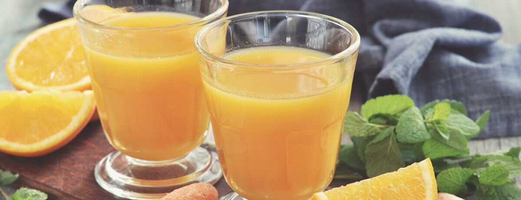 a photo of two glasses of carrot orange drink sitting side by side