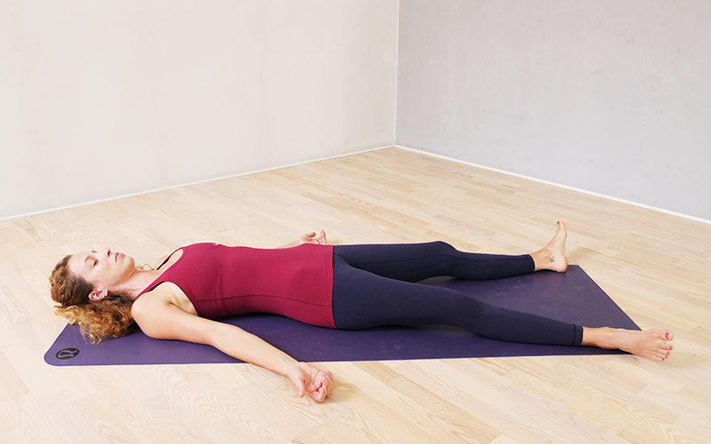 A white woman with curly dark blonde hair performs savasana on the floor on a yoga mat indoors.