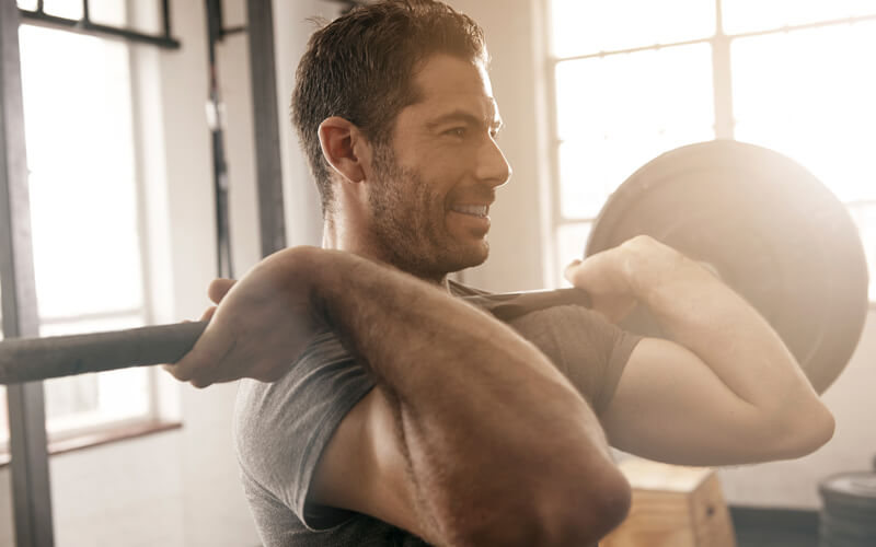 A white man holds a barbell on his chest as part of a muscle building workout plan