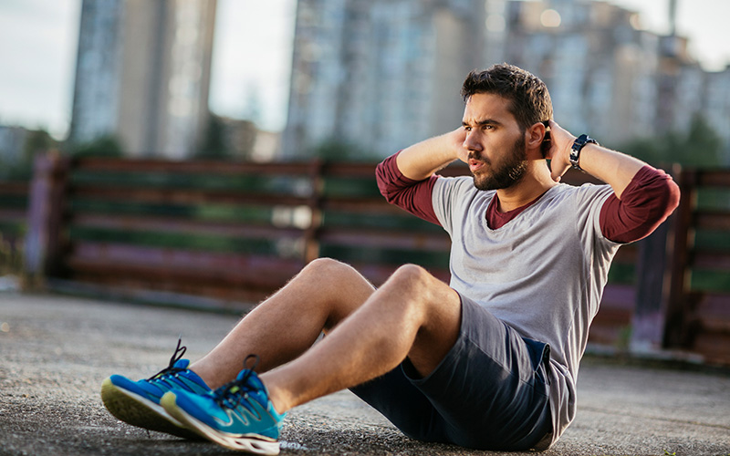 A white, dark-bearded man does sit-ups outdoors with skyscrapers visible behind him