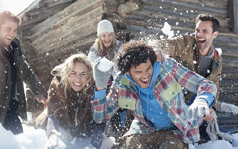 A group of adult friends laughs during a snowball fight.