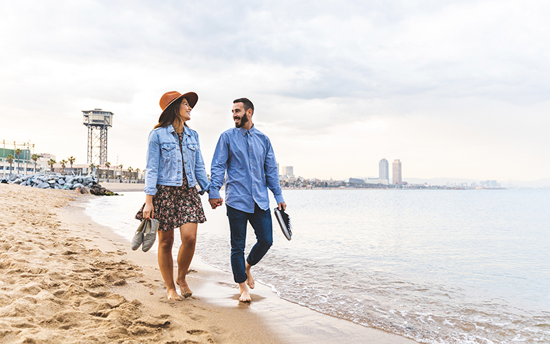 A white couple walks on the beach, holding hands and gazing at each other.