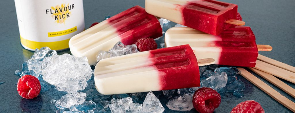 A collection of banana raspberry ice pops on a bed of ice cubes, with a jar of Flavor Kick behind them