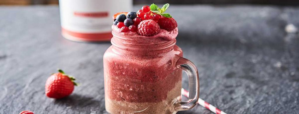 A chocolate berry shake in a Mason jar topped with fresh and bright berries