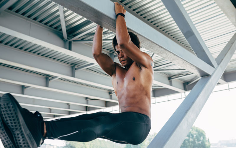 A shirtless man of color in black leggings performs flexibility exercises while hanging from an outdoor ceiling