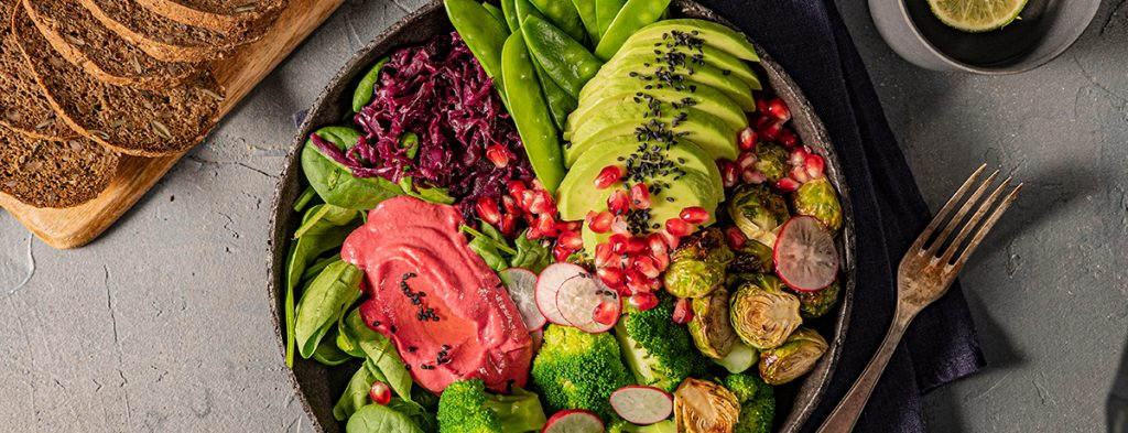 A color-packed winter Buddha bowl with avocado slices, pomegranate seeds, beetroot hummus, Brussels sprouts, and more