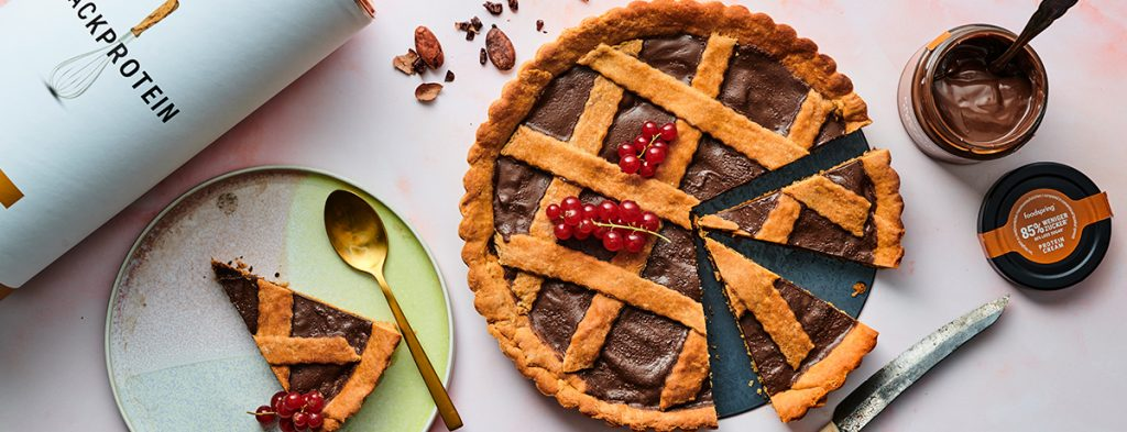 photo of a chocolate-filled crostata tart, with a slice set aside on its own plate and an open jar of Hazelnut Protein Cream sitting on the other side of the tart.