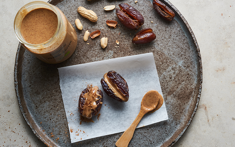 Two peanut-butter-filled date snacks sit on a piece of parchment paper, laid on a gray-brown plate.