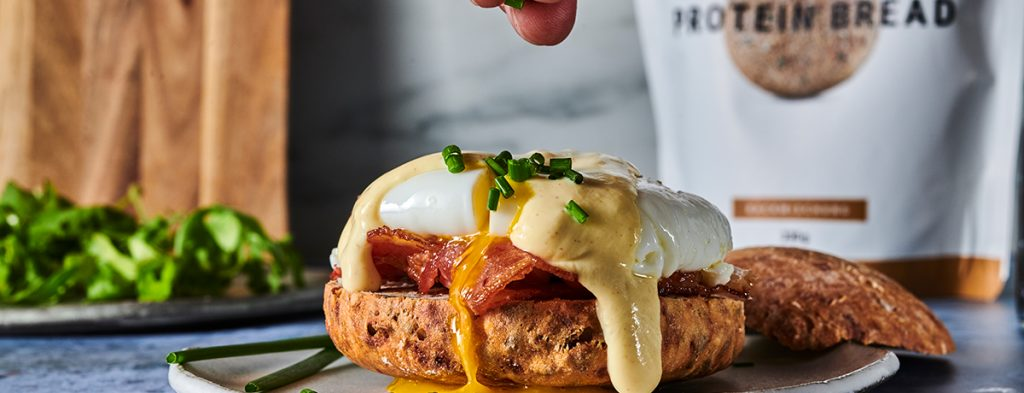 Eggs Benedict on a plate. The yellow hollandaise sauce is oozing over the sides of the slice of protein bread. There is a package of foodspring's protein bread in the background.